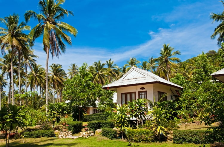 Tropical white beach house surrounded by palm trees on the island Koh Kood, Thailand.