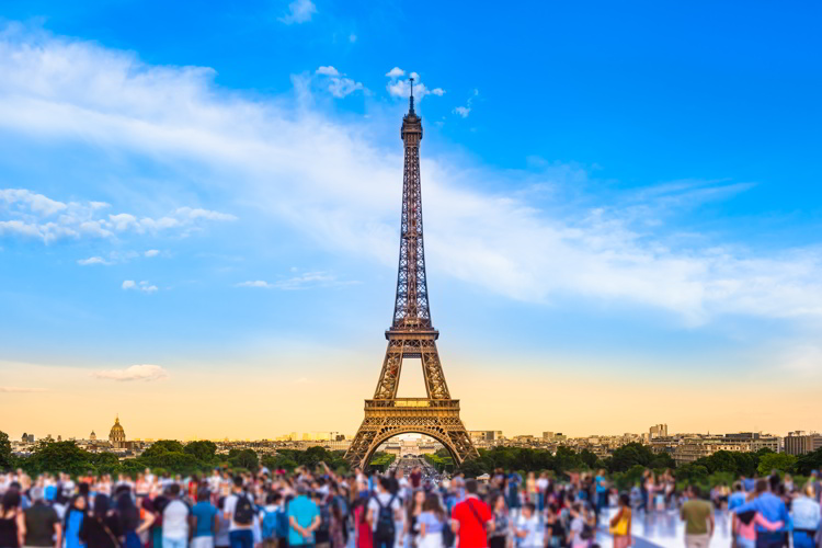 Colorful large group of unrecognizable people blurred in front of Paris Eiffel Tower at evening