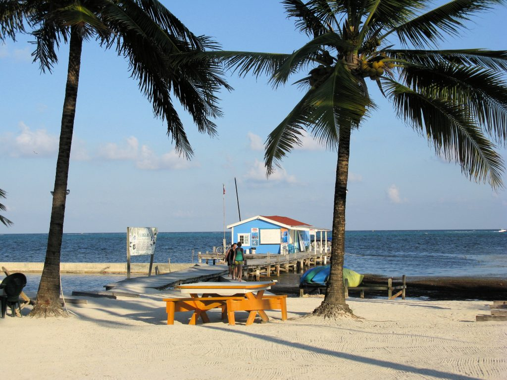 A colorful dock on a white sand beach