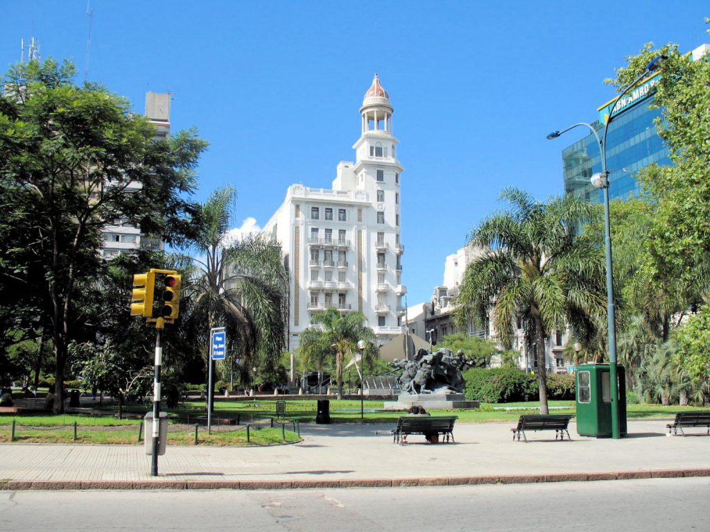 A plaza with trees, a bronze sculpture and buildings in Montevideo Uruguay