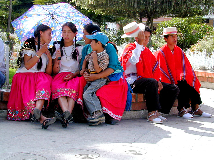 Women and men dressed in colorful local attire sit in a park in Cuenca