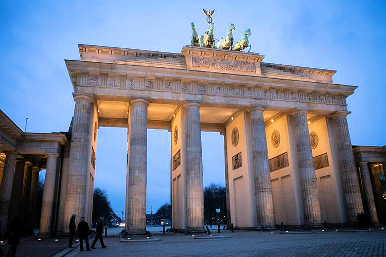 A view of thelit up Brandenberg Gate at dusk