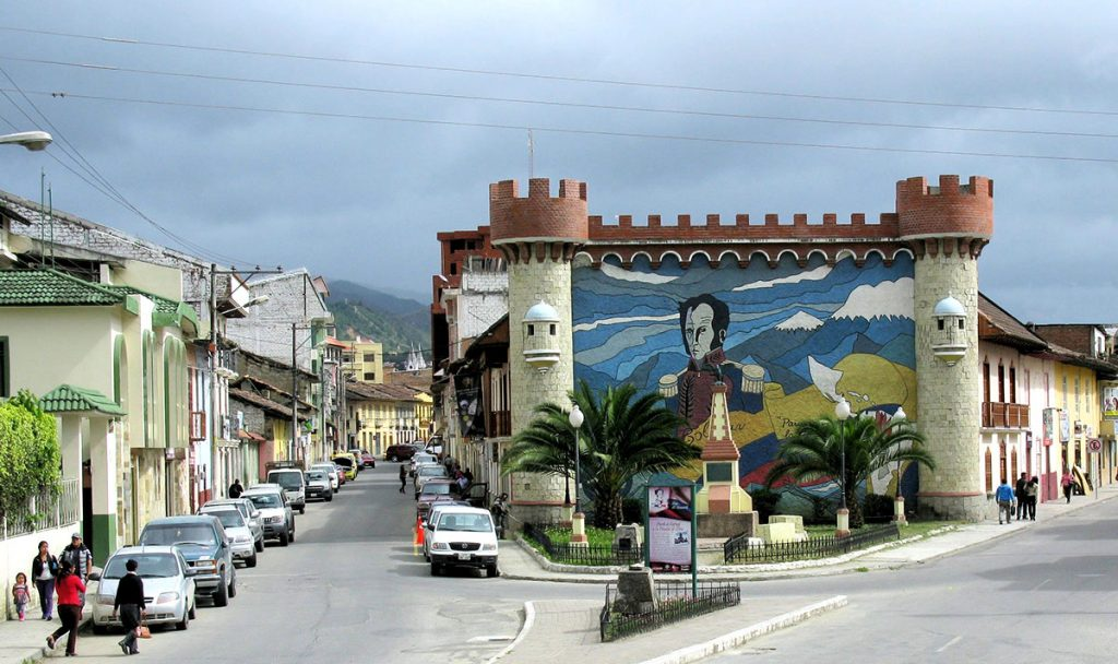 a plaza with a castle looking building with a large mural of Simon Bolivar on it
