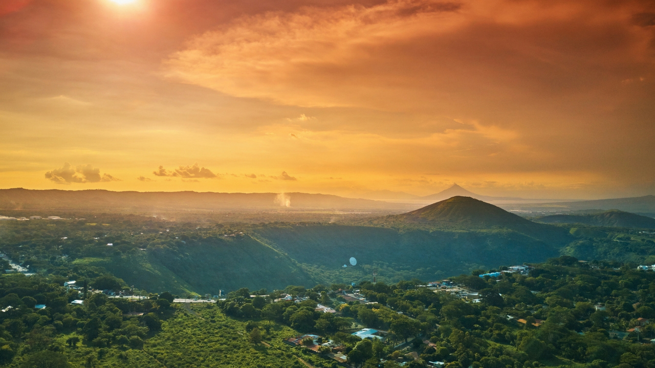 Nicaraguan Mountains. Sunsest over a mountain town as panoramic shows scattered houses and mountain ranges in the distance