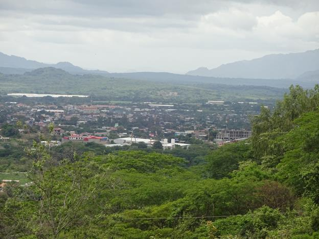 A panoramic view of Esteli. This town is surrounded by green mountains which rise up in the distance.