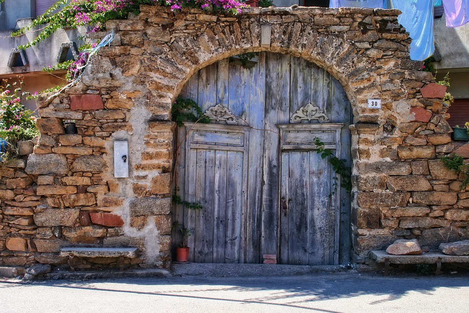 Image of an old gate in sardinia. the gate is wooden and the wall and ark in old stone