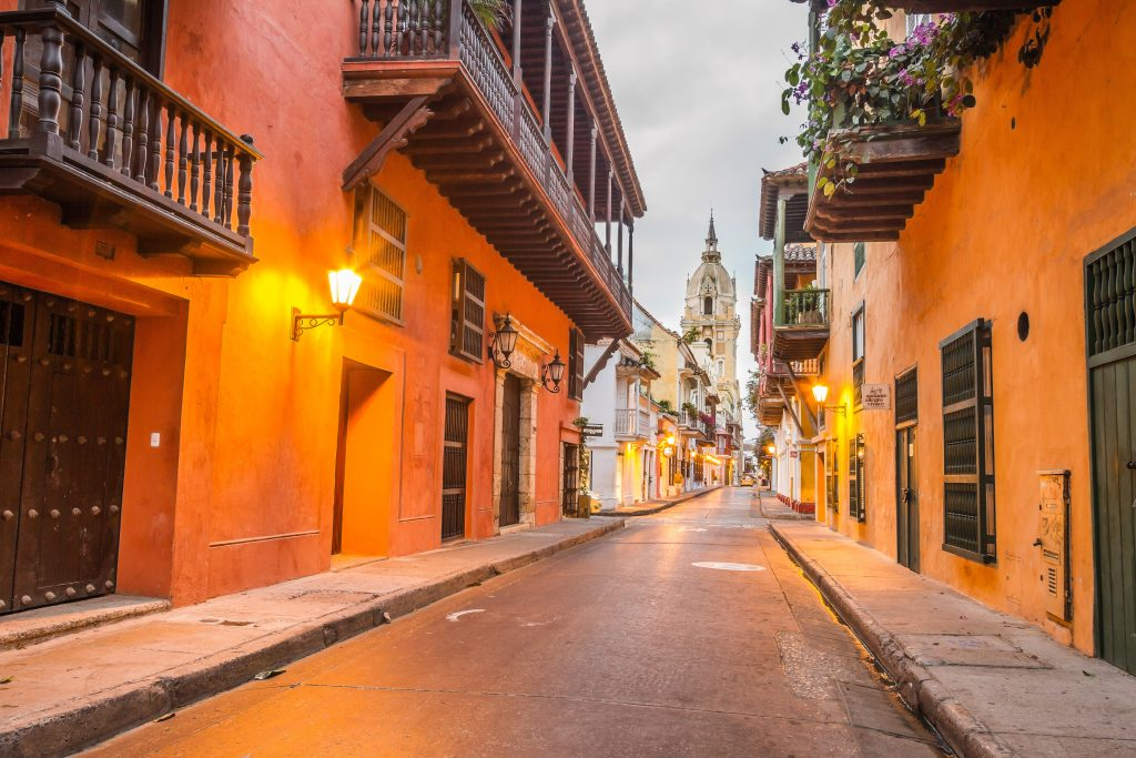 Image of a street in the walled city of cartagena, colombia. Orange houses line a wide open road with a church spire in the background