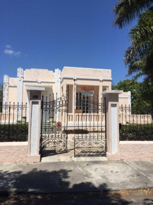 mansion in merida, mexico for sale at over 1 million dollars. mansion is light stone and sits behind ornate gates