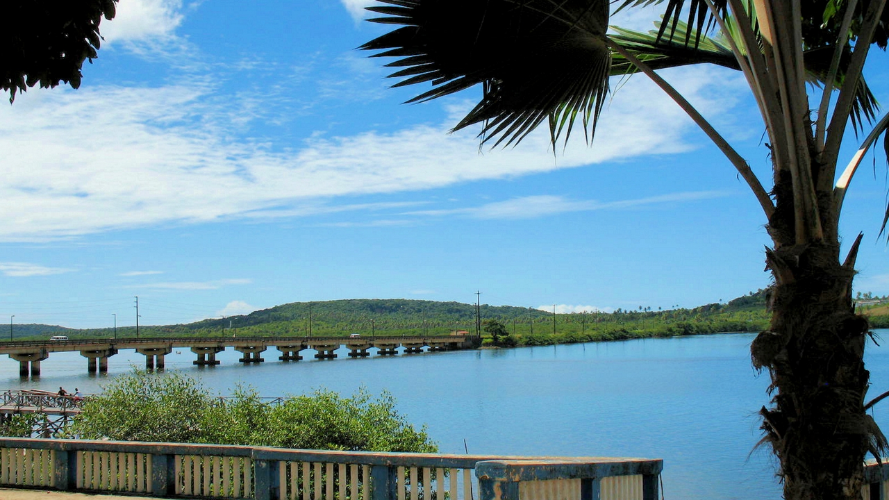 View of a bridge extending out across the water towards the lush island of Itamaraca, Brazil