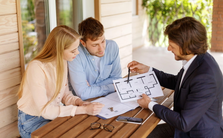 Real estate agent showing house plan to a couple at table on porch