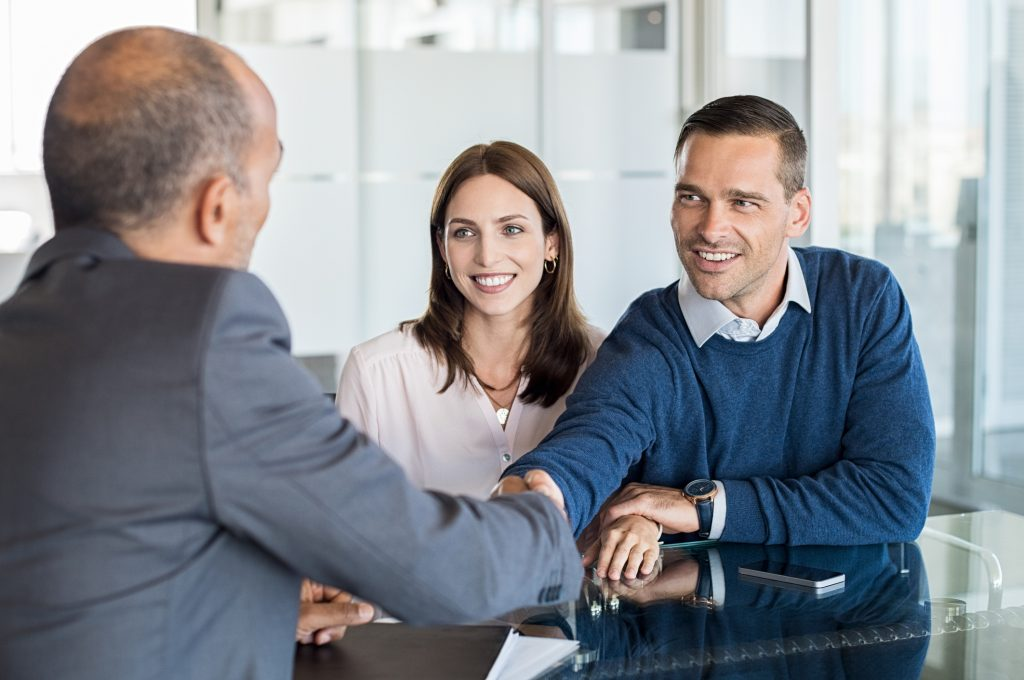 Businessman shaking hand with a young couple in office. Bank agent and his client shaking hands in conference room. Happy smiling couple seal a deal with their personal financial advisor.