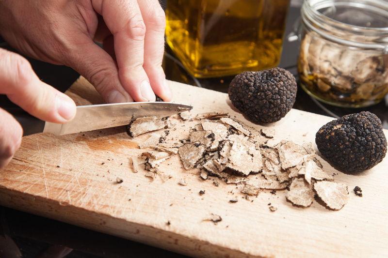 Black truffles being cut by a knife on a chopping board