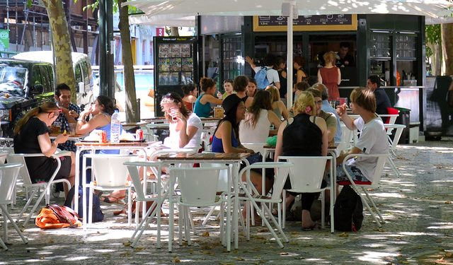 People sit outside a cafe in Avenida da Liberdade, Lisbon