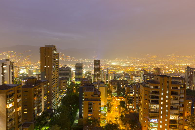 Aerial view of Medellin at night with residential and office buildings.