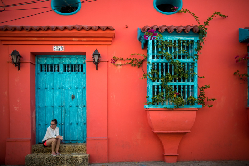 A woman sits on the steps of a house in Cartagena, Colombia.