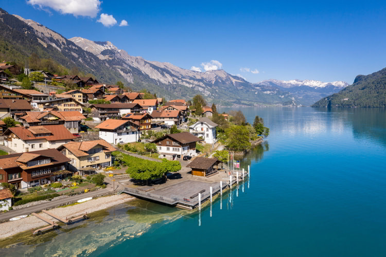 Idyllic Oberried village by the alpine lake Brienz in Bern, Switzerland on a sunny day.