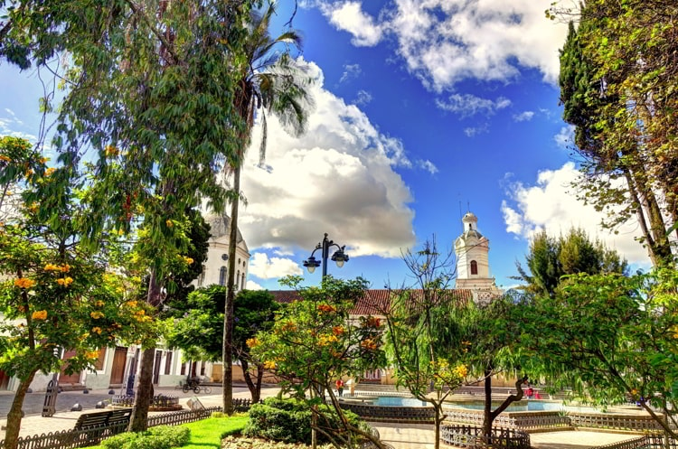 Sunny day in Cuenca, Ecuador. Green trees with a white church on the background.